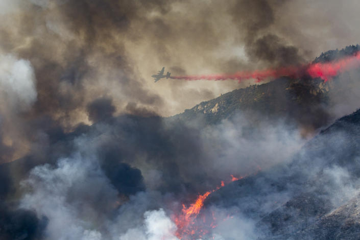 An air tanker drops retardant at a wildfire burns at a hillside in Yucaipa, Calif., Saturday, Sept. 5, 2020.  (AP Photo/Ringo H.W. Chiu)