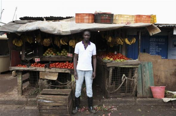 Karl Moi Okoth, a 27 year-old vegetable and fruit seller, poses in front of his makeshift shop in Nairobi's Kibera slum in the Kenyan capital, April 30, 2012. Okoth studied psychology and chemistry at Day Star University where he received a degree in psychology. He has been searching for permanent employment for four years but has decided to make a living working in the slums for the last eight months. Picture taken April 30, 2012.