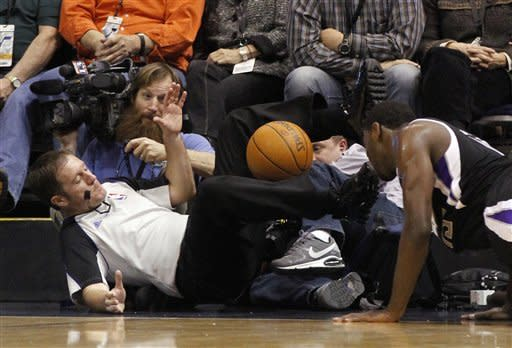Referee Brent Barnaky, left, falls into the media after being knocked down by Sacramento Kings guard Tyreke Evans during the second half of an NBA basketball game against the Utah Jazz, Saturday, Jan. 28, 2012, in Salt Lake City. The Utah Jazz won 96-93. (AP Photo/Jim Urquhart)