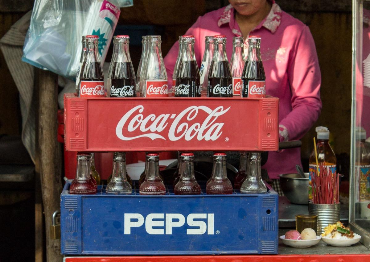"""No matter where you go, it's comforting to know you can always enjoy a Coca-Cola. Well, <em>almost </em>anywhere. While this fizzy drink is sold practically everywhere, it still hasn't (officially) made its way to North Korea or Cuba, according to the <a href=""""https://www.bbc.com/news/magazine-19550067"""" target=""""_blank"""">BBC</a>. That's because these countries are under long-term U.S. trade embargoes.  However, some folks say <a href=""""https://www.thestar.com/news/world/2017/04/20/coca-cola-bubbling-up-in-north-korea-and-its-usually-not-the-real-thing.html"""" target=""""_blank"""">you might be able</a> to snag a sip of the stuff if you try hard enough (although it'll typically be a <em>lot</em> more expensive than what you would pay in the states—and probably imported from a neighboring country such as Mexico or China)."""