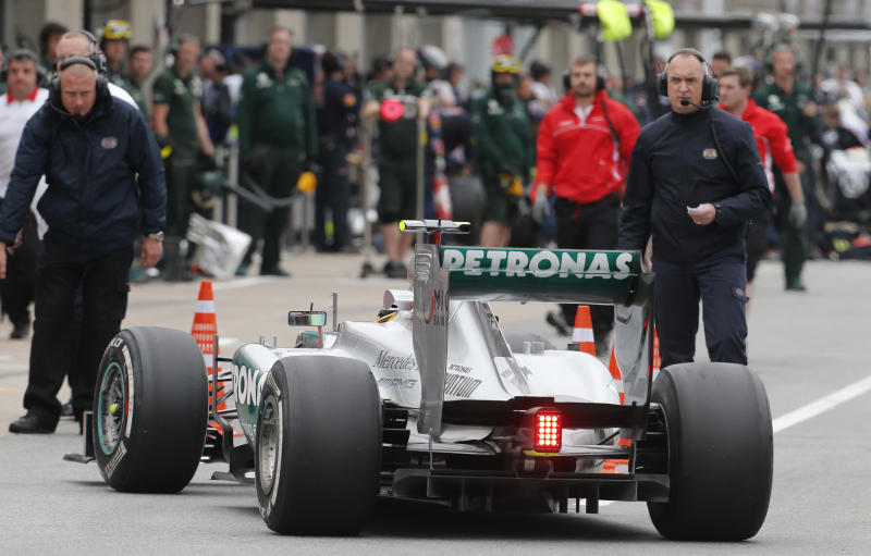 FILE - In this Friday, June 7, 2013 file photo, Mercedes driver Lewis Hamilton of Britain backs to the pits as FIA members watch at the end of the second practice session at the Gilles Villeneuve racetrack, in Montreal, Canada. A tire testing session involving Mercedes and Pirelli that was criticized by rival Formula One teams will be referred to the FIA's international tribunal as a possible breach of the sport's rules. (AP Photo/Luca Bruno, File)