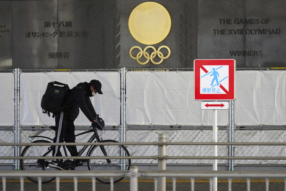 A man wearing a face mask to protect against the spread of the coronavirus rides a bicycle near the Japan National Stadium, where opening ceremony and many other events are planned for postponed Tokyo 2020 Olympics, as engravings in honor of 1964 Tokyo Olympics are seen on the side of the stadium wall behind the fence in Tokyo Monday, Jan. 18, 2021. The Japanese capital confirmed more than 1,200 new coronavirus cases on Monday. (AP Photo/Eugene Hoshiko)