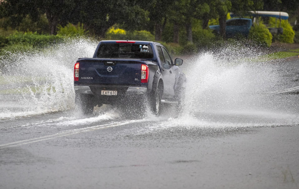 A vehicle plows through water on a flooded road at Port Stephens, 200 kilometers (120 miles) north of Sydney, Australia, Sunday, March 21, 2021. Residents across the state of New South Wales have been warned to prepare for possible evacuations, as NSW Premier Gladys Berejiklian said the state's flood crisis would continue for several more days. (AP Photo/Mark Baker)