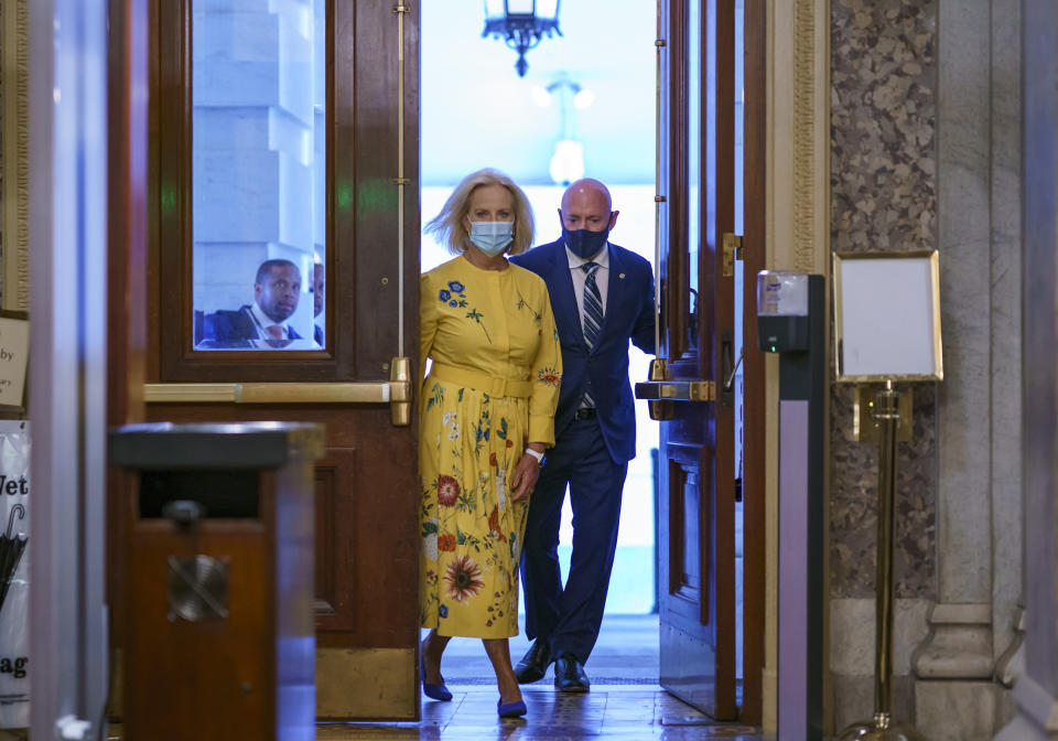 Sen. Mark Kelly, D-Ariz., is joined by Cindy McCain, left, the widow of the late Senator John McCain of Arizona, as Kelly arrives to deliver his maiden speech to the Senate, at the Capitol in Washington, Wednesday, Aug. 4, 2021. (AP Photo/J. Scott Applewhite)