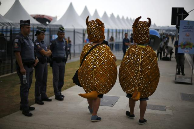 Supporters of Brazil's national soccer team wear costumes as walk past police at the Corinthians arena in Sao Paulo, one day before the match of the soccer World Cup between Uruguay and England, June 18, 2014. REUTERS/Ivan Alvarado (BRAZIL - Tags: CRIME LAW SOCCER SPORT WORLD CUP)