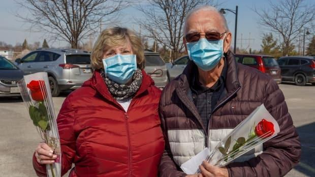Tony Oliver, right, with his wife Norma Oliver holding roses after their vaccinations.