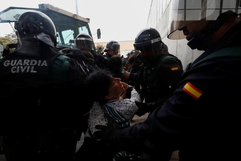 Spanish Civil Guard officers scuffle with a woman outside a polling station for the banned independence referendum. (Juan Medina / Reuters)