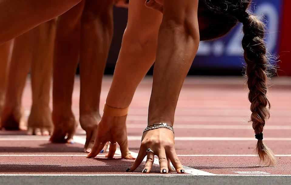 A closeup of women's hands, fingertips pressed into the ground, and one woman's braid, at the starting line.