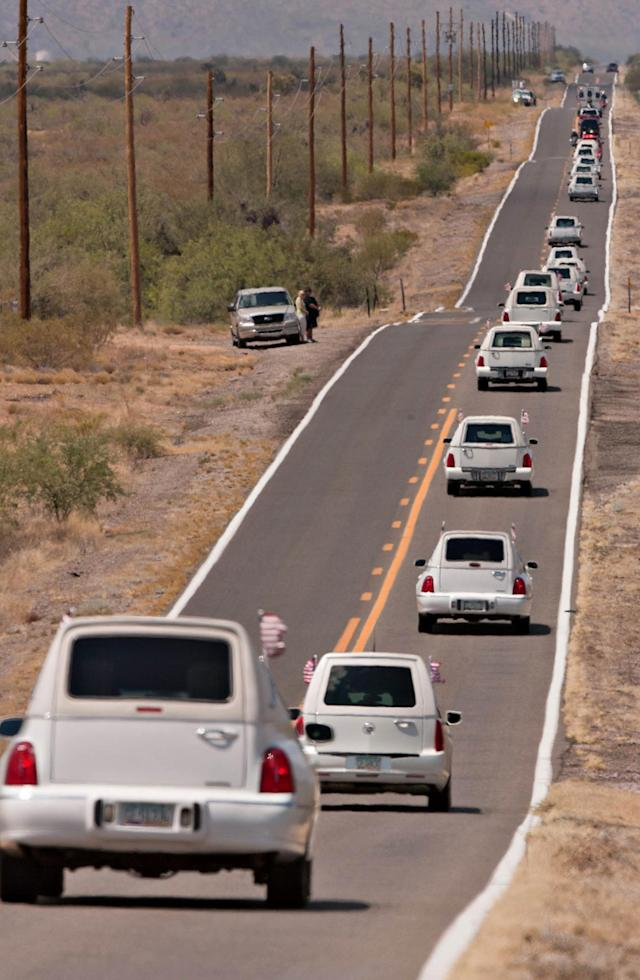 A line of hearses makes their way north on Highway 89, south of Congress, Ariz. as the bodies of the 19 members of the Granite Mountain Hotshots were returned to Prescott, Ariz. from Phoenix, Sunday, July 7, 2013. (AP Photo/The Arizona Republic, Tom Story)