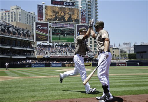 San Diego Padres' Chris Denorfia, left, is congratulated by Chase Headley after his first-inning home run against the San Francisco Giants in a baseball game in San Diego, Sunday, July 14, 2013. (AP Photo/Lenny Ignelzi)