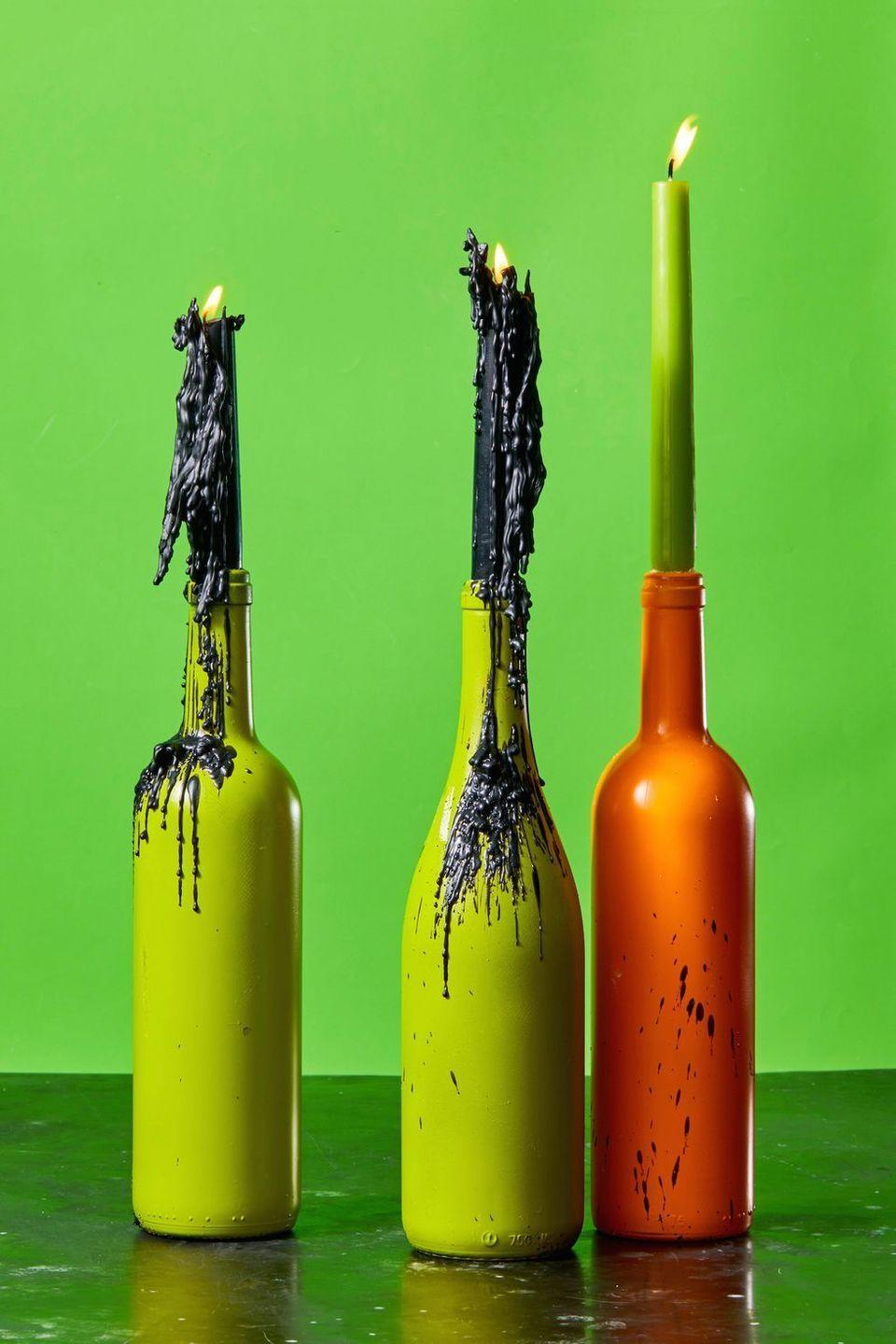 """<p>Make basic candlesticks just a little bit creepy for a standout centerpiece. Start by spray painting old wine bottles in orange and green and filling them with candlesticks. You can even let wax drip to make more of an impact. <br></p><p><a class=""""link rapid-noclick-resp"""" href=""""https://go.redirectingat.com?id=74968X1596630&url=https%3A%2F%2Fwww.etsy.com%2Flisting%2F711505565%2Fgreen-4-chime-candles-set-of-10-spell&sref=https%3A%2F%2Fwww.goodhousekeeping.com%2Fholidays%2Fhalloween-ideas%2Fg33437890%2Fhalloween-table-decorations-centerpieces%2F"""" rel=""""nofollow noopener"""" target=""""_blank"""" data-ylk=""""slk:SHOP CANDLESTICKS"""">SHOP CANDLESTICKS</a></p>"""