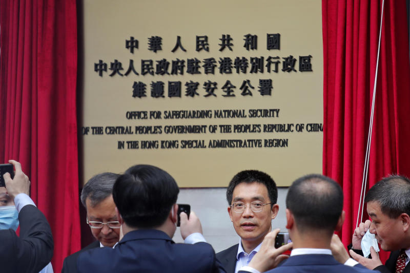 Mainland Chinese Communist Party officials and Hong Kong officials attend an opening ceremony for China's new Office for Safeguarding National Security in Hong Kong, Wednesday, July 8, 2020. China's new national security office in Hong Kong got off to an early start on Wednesday with an official opening amidst heavy police presence. (AP Photo/Kin Cheung)