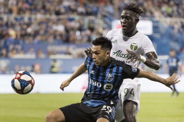 Montreal Impact's Mathieu Choiniere, left, and Portland Timbers' Modou Jadama move in on the ball during the second half of an MLS soccer match in Montreal, Wednesday, June 26, 2019. (Graham Hughes/The Canadian Press via AP)