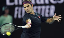 Switzerland's Roger Federer makes a forehand return to United States' Steve Johnson during their first round singles match the Australian Open tennis championship in Melbourne, Australia, Monday, Jan. 20, 2020. (AP Photo/Lee Jin-man)