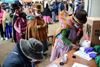 An indigenous woman signs after casting her vote at a polling station in Huarina, Bolivia
