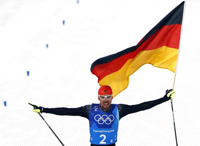 Nordic Combined Events - Pyeongchang 2018 Winter Olympics - Men's Team 4 x 5 km Final - Alpensia Cross-Country Skiing Centre - Pyeongchang, South Korea - February 22, 2018 - Johannes Rydzek of Germany waves the German flag as he approaches the finish line. REUTERS/Dominic Ebenbichler