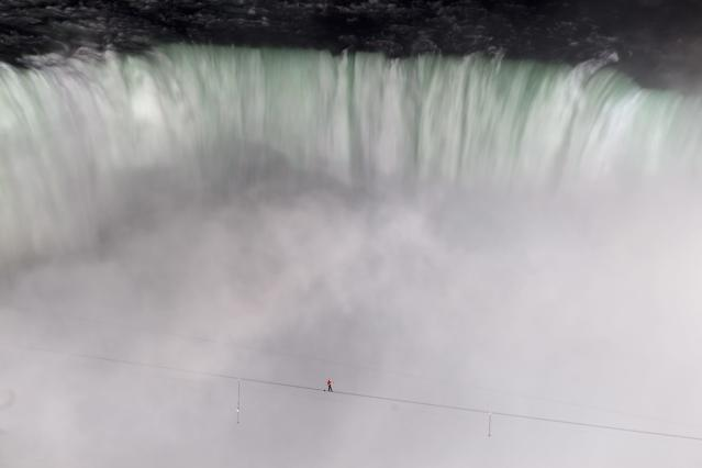 Nik Wallenda walks over Niagara Falls on a tightrope as seen from Niagara Falls, Ontario, on Friday, June 15, 2012. Wallenda has finished his attempt to become the first person to walk on a tightrope 1,800 feet across the mist-fogged brink of roaring Niagara Falls. The seventh-generation member of the famed Flying Wallendas had long dreamed of pulling off the stunt, never before attempted. (AP Photo/The Canadian Press, Frank Gunn)