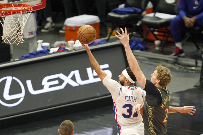 Philadelphia 76ers' Seth Curry, left, drives to the basket past Chicago Bulls' Lauri Markkanen, right, during the first half of an NBA basketball game Monday, May 3, 2021, in Chicago. (AP Photo/Charles Rex Arbogast)