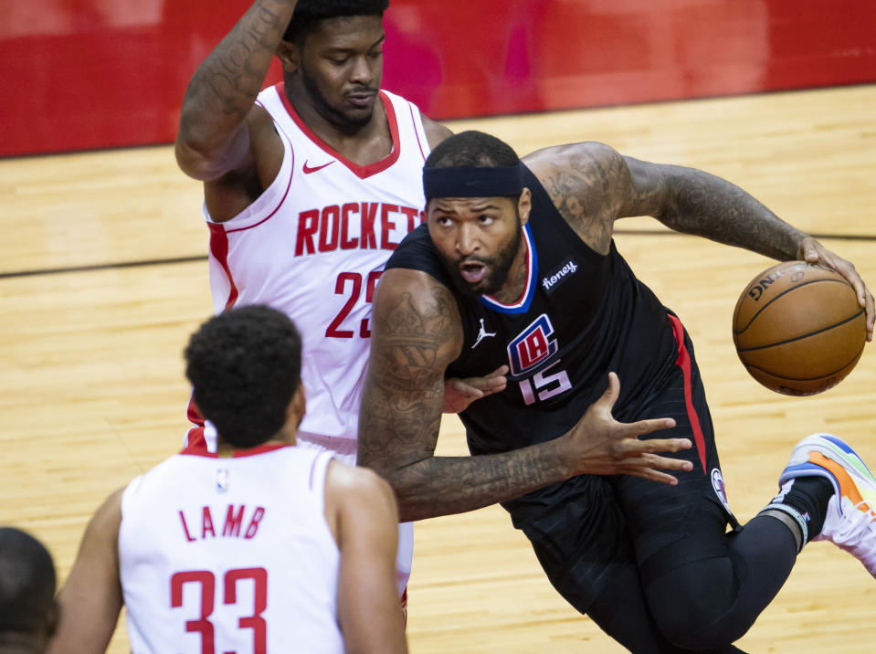 LA Clippers center DeMarcus Cousins (15) drives around Houston Rockets forward Cameron Oliver (25) during the first quarter of an NBA game Friday, May 14, 2021, in Houston. (Mark Mulligan/Houston Chronicle via AP)