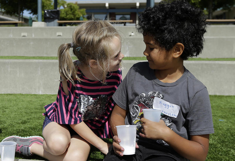 """In this Tuesday, July 11, 2017 photo, campers Gracie, left, leans toward Nugget during an activity at the Bay Area Rainbow Day Camp in El Cerrito, Calif. The camp caters to transgender and """"gender fluid"""" children, aged 4-12, making it one of the only camps of its kind in the world open to preschoolers, experts say. Nugget's name tag also includes preferred pronouns. (AP Photo/Jeff Chiu)"""