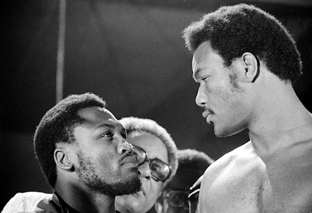 FILE - In this file photo taken Jan. 22, 1972, defending WBA champion Joe Frazier, left, and challenger George Foreman have a close look at each other as they meet during the weigh-in moments before their world heavyweight boxing title bout at National Stadium in Kingston, Jamaica. The former heavyweight champion has died after a brief final fight with liver cancer. He was 67. The family issued a release confirming the boxer's death on Monday, Nov. 7, 2011. (AP Photo/File)