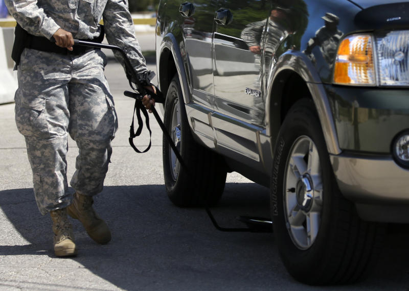 A vehicle is inspected before nearing the Lawrence H. WIlliams Judicial Center as a pretrial hearing gets underway, Tuesday, July 9, 2013, in Fort Hood, Texas. Jury selection is set to start Tuesday in the long-awaited murder trial of Army psychiatrist Maj. Nidal Hasan, accused of opening fire with a semi-automatic gun at Fort Hood nearly four years ago. (AP Photo/Tony Gutierrez)