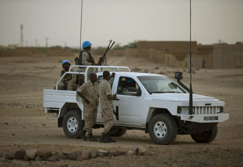 In this July 28, 2013 photo, United Nations peacekeepers stand guard at a polling station, during presidential elections in Kidal, Mali. A bomb explosion killed several members of the U.N. peacekeeping mission in Mali in the troubled northern city of Kidal, a spokesman for the mission said Saturday, Dec. 14, 2013. (AP Photo/Rebecca Blackwell)