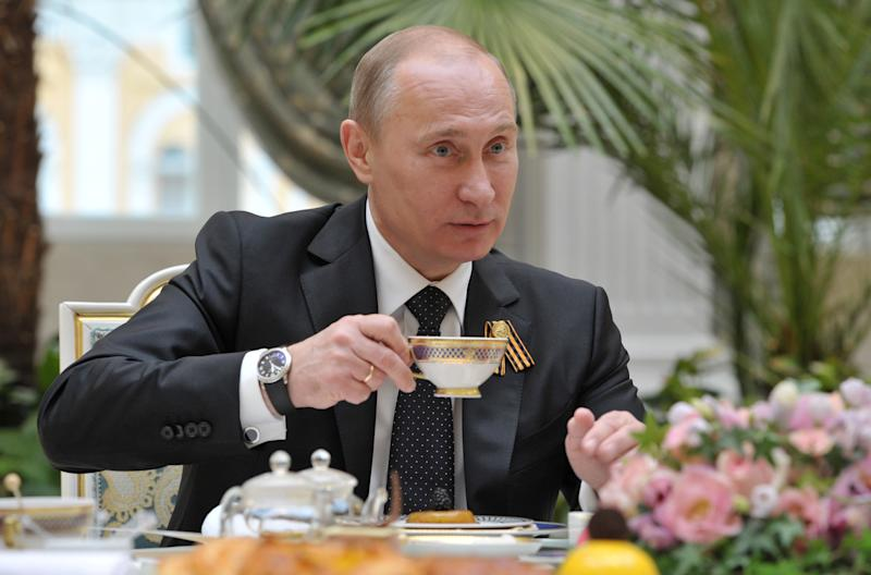 Russian President Vladimir Putin holds a cup of  tea as he meets with Sonya, 8, not pictured, from the city of Pskov in Moscow's Kremlin on Wednesday, May 9, 2012. Sonya undergoes a medical treatment  at Federal Scientific Center for Child's Oncology in Moscow. (AP Photo/RIA Novosti, Alexei Druzhinin, Government Press Service)