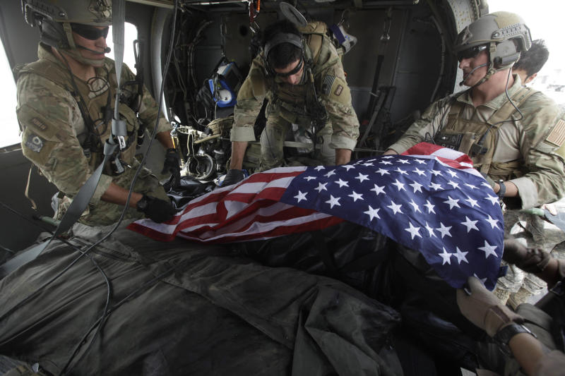 FILE- In this file photograph made on July 29, 2010, upon landing after a helicopter rescue mission, Tech. Sgt. Jeff Hedglin, right, an Air Force Pararescueman, or PJ, drapes an American flag over the remains of the first of two U.S. soldiers killed minutes earlier in an IED attack, assisted by fellow PJs, Senior Airman Robert Dieguez, center, and 1st Lt. Matthew Carlisle, in Kandahar province, southern Afghanistan. U.S. military deaths in Afghanistan have surpassed 2,000, a grim reminder that a war which began nearly 11 years ago shows no signs of slowing down despite an American decision to begin the withdrawal of most of its combat forces. (AP Photo/Brennan Linsley, File)