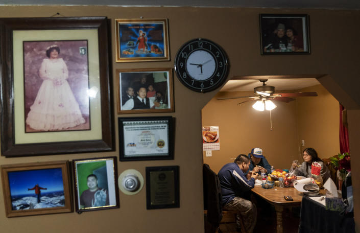 Mario Valdez, 62, center, eats dinner with his wife, Reyna, 52, right, and their son Axel, 18, at their home in Central Falls, R.I., Thursday, Feb. 18, 2021. The three were fully vaccinated for COVID-19 this month as part of a special effort to inoculate every resident of Central Falls, the Rhode Island community hit hardest by the pandemic. (AP Photo/David Goldman)