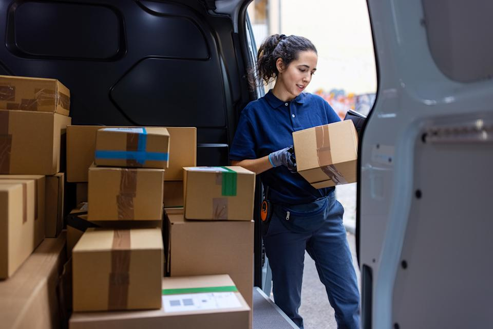 Female courier standing by shipping van checking the parcel for delivery. Woman looking at the delivery address of the parcel in van.