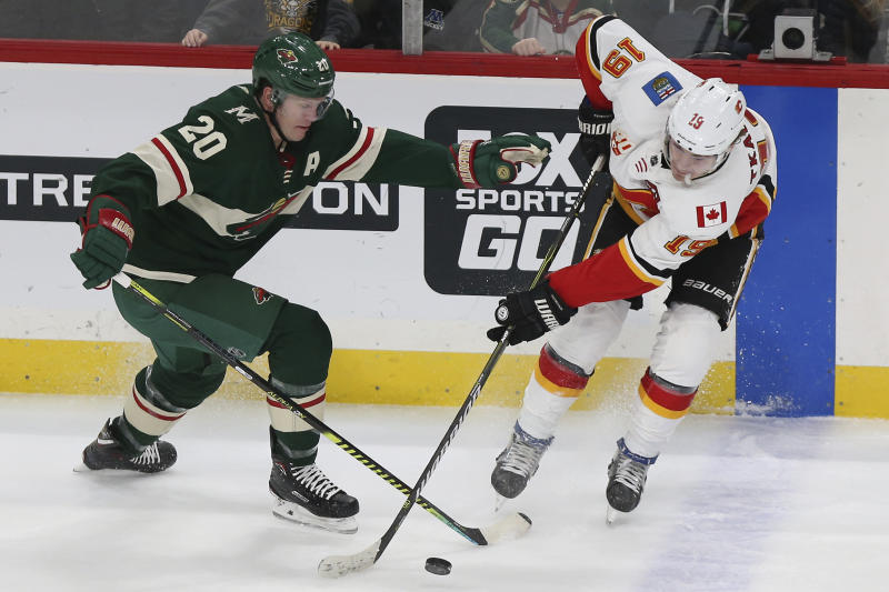 Minnesota Wild's Ryan Suter and Calgary Flames' Matthew Tkachuk go after the puck in the third period of an NHL hockey game Monday, Dec. 23, 2019, in St. Paul, Minn. Minnesota won 3-0. (AP Photo/Stacy Bengs)