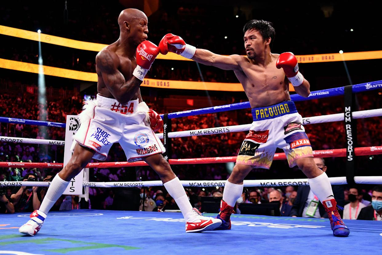 Manny Pacquiao (R) of the Philippines fights against Yordenis Ugas of Cuba during the WBA Welterweight Championship boxing match at T-Mobile Arena in Las Vegas, Nevada on August 21, 2021. (Photo by Patrick T. FALLON / AFP) (Photo by PATRICK T. FALLON/AFP via Getty Images)