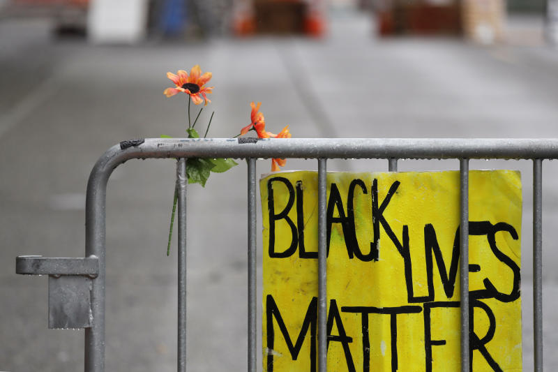 A barricade stands at the end of a street where a plywood-covered and closed Seattle police precinct stands Tuesday, June 9, 2020, in Seattle, following protests over the death of George Floyd, a black man who was in police custody in Minneapolis. Under pressure from city councilors, protesters and dozens of other elected leaders who have demanded that officers dial back their tactics, the police department on Monday removed barricades near its East Precinct building in the Capitol Hill neighborhood, where protesters and riot squads had faced off nightly. Protesters were allowed to march and demonstrate in front of the building, and the night remained peaceful. (AP Photo/Elaine Thompson)