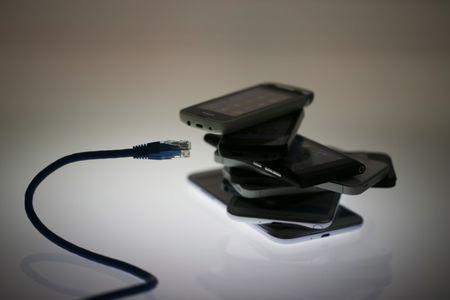 An illustration picture shows a network cable next to a pack of smartphones in Berlin