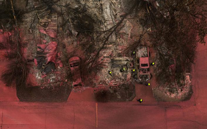 A search and rescue team, surrounded by red fire retardant, look for victims under burned residences and vehicles in the aftermath of the Almeda fire in Talent, Oregon, U.S., September 13, 2020. Picture taken with a drone.