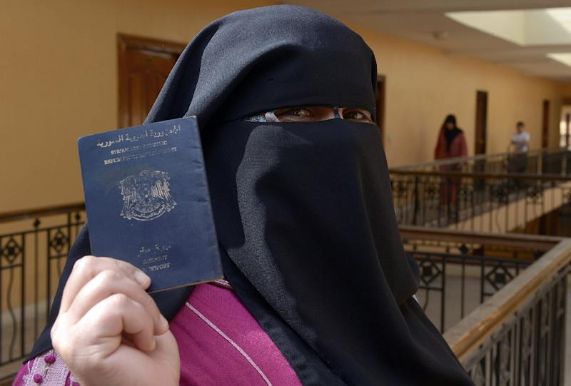 Fatima, a 45-year-old Syrian refugee from the central city of Homs, flashes her passport in Tangier, Morocco, on October 28, 2013 (AFP Photo/Fadel Senna)