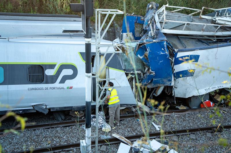A man looks at the damage on an intercity passenger train after it rammed into a maintenance vehicle (AP)