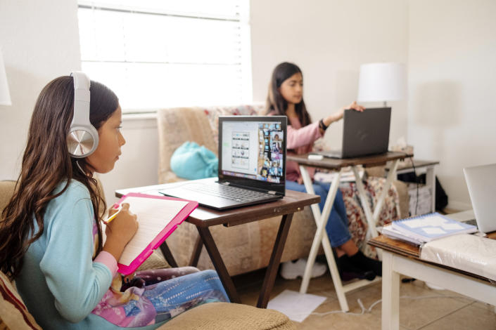 Two girls attending school virtually from home. (Photo: Getty Images)