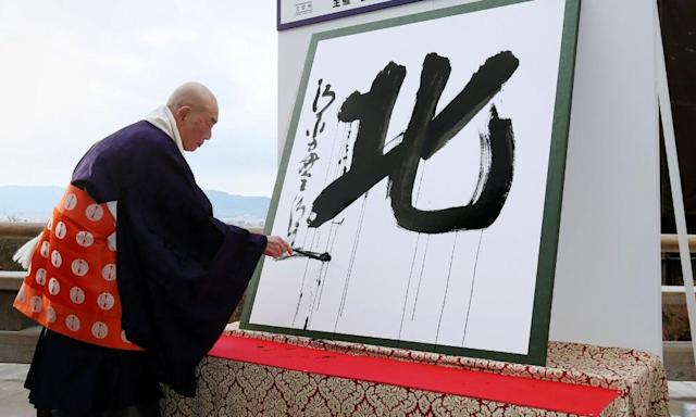 "<span class=""element-image__caption"">Seihan Mori, master of the ancient Kiyomizu temple, uses an ink-soaked calligraphy brush to write the kanji for north.</span> <span class=""element-image__credit"">Photograph: -/AFP/Getty Images</span>"