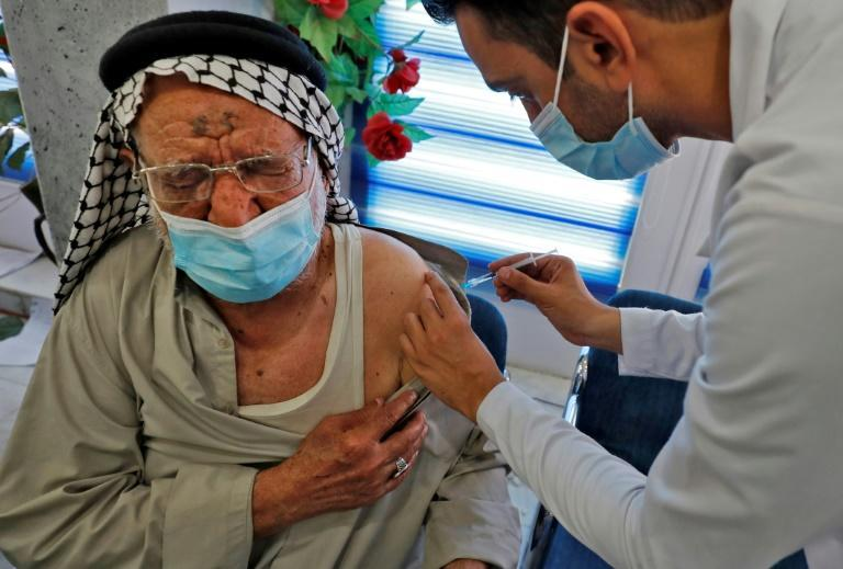 An elderly Iraqi man grimaces as he gets a Covid jab