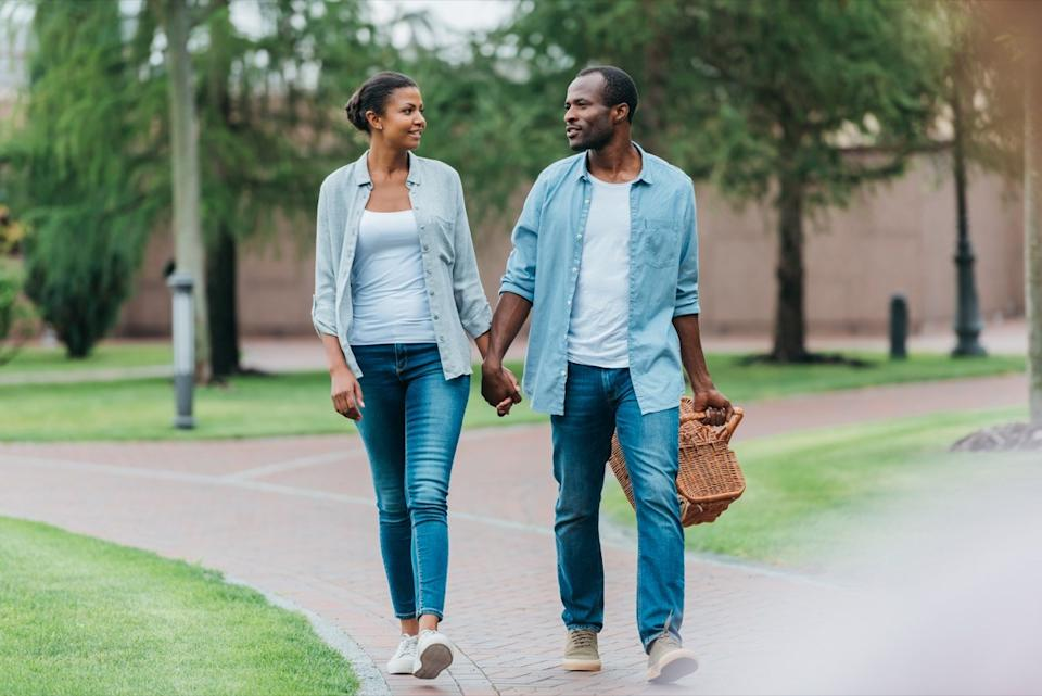 Couple walking in park together with a picnic basket