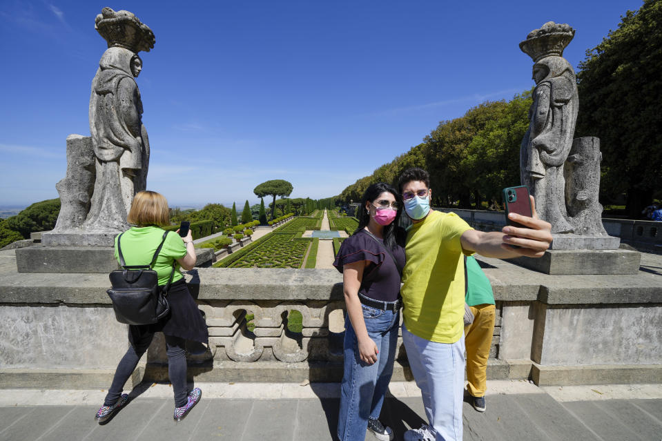Visitors take selfie photos in the gardens of the Papal Palace, in Castel Gandolfo, Saturday, May 29, 2021. As Covid-19 restrictions are slowly being lifted in Italy, thousands of people are returning to see the extensive gardens and apartments at the Papal Palace of Castel Gandolfo in the Alban Hills near Rome, that for hundreds of years have been the summer retreat for Popes seeking to escape the suffocating heat of Rome. (AP Photo/Andrew Medichini)
