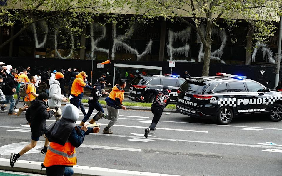 Demonstrators hit a police car during a protest against Covid regulations in Melbourne today - AFP via Getty Images