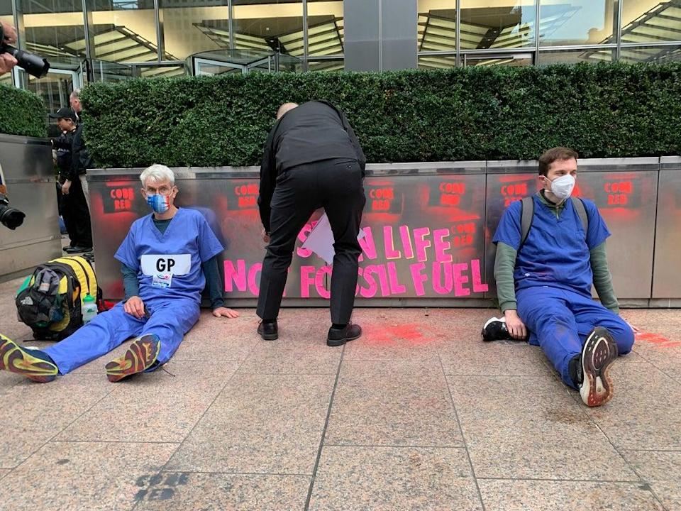 A police officer removes sticky notes put up by XR as two GPs sit glued to the ground outside JP Morgan's building (The Independent)