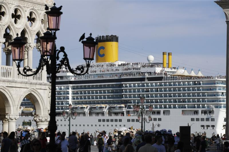 A cruise ship passes by St. Mark's Square filled with tourists, in Venice, Italy, Sunday, June 2, 2019. Groups that want to ban cruise ships on Venice's busy canals say a collision that injured four tourists has served as a wake-up call. Opponents say cruise ships are out-of-scale for Venice, cause pollution, threaten the lagoon's ecosystem and dangerous. (AP Photo/Luca Bruno)