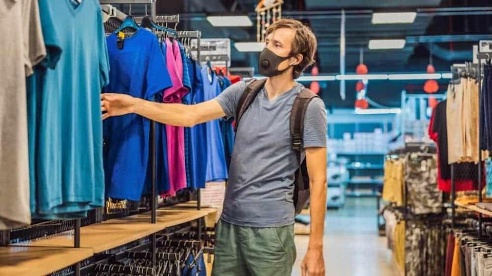 Man in a clothing store in a medical mask because of a coronovirus.