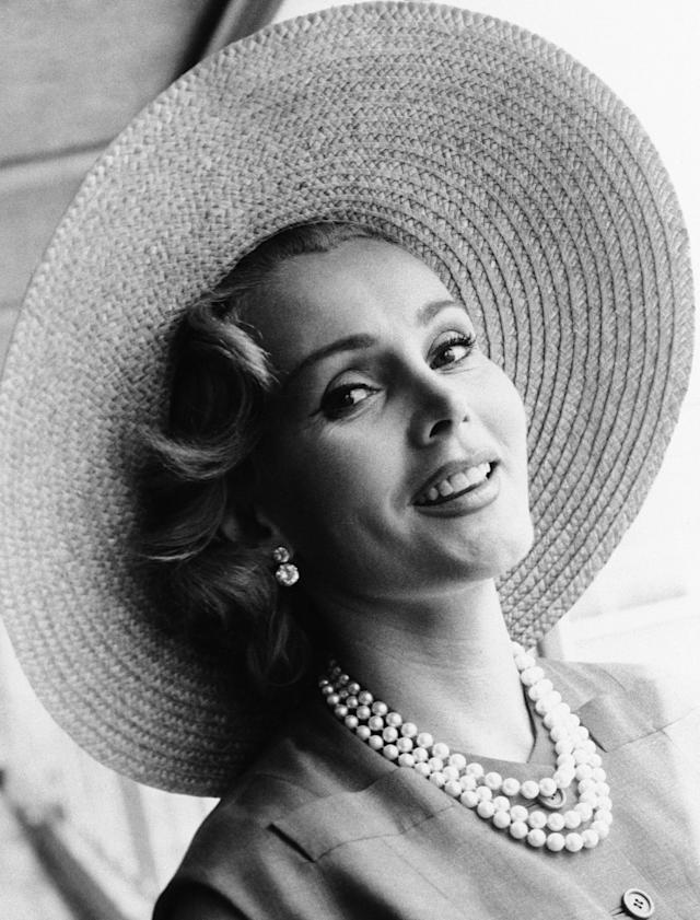 <p>Hungarian born actress Zsa Zsa Gabor was as well known for her on-screen performances as she was for her off-screen romances. Married nine times, the socialite died at 99 on December 18. — (Pictured) Zsa Zsa Gabor arrives at London Airport from Paris, in a Crimson dress and a straw hat in 1955. (AP Photo) </p>