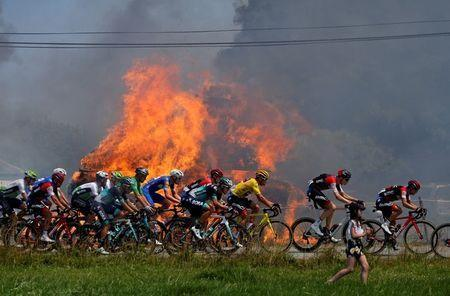 The peloton passes hay bales on fire during the 181-km Stage 6 from Brest to Mur-de-Bretagne Guerleden during the Tour de France, July 12, 2018. REUTERS/Stephane Mahe