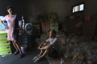Yu Ruiping, left, and her husband Lu Jinlin, middle, rest in a family warehouse with pickled vegetables that they salvaged from the floods in Xinxiang in central China's Henan Province, Monday, July 26, 2021. Record rain in Xinxiang last week left the couple's goods in a nearby market underwater, causing losses that could run into the tens of thousands of dollars. Dozens of people died in the floods that immersed large swaths of central China's Henan province in water. (AP Photo/Dake Kang)